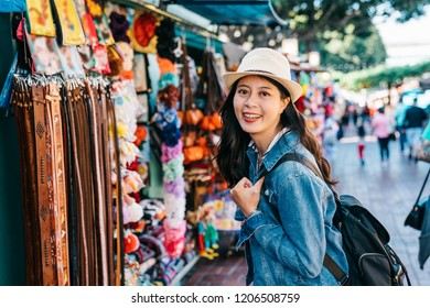 pretty lady is standing in front of the belt vendor and choosing the gift for her husband. young traveler buying souvenir in famous Mexican street in LA. girl tourist face to camera smiling.