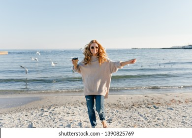 Pretty lady in sweater running around sea coast. Well-dressed blonde girl drinking coffee at beach