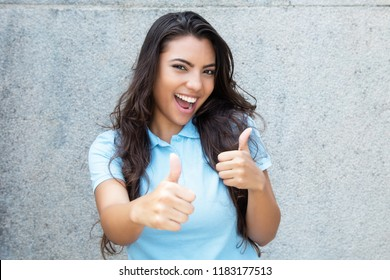 Pretty latin american woman with long hair showing both thumbs up outdoors in summer