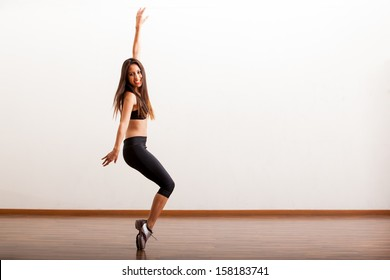 Pretty Latin female dancer rehearsing a tap routine in a dance academy