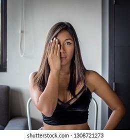 Pretty latina girl in black tank top making cute facial expression.