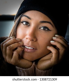 Pretty latina girl close up wearing beanie. Beautiful face.