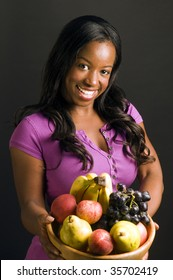 pretty latina hispanic african american woman smiling and offering bowl of healthy fresh fruit