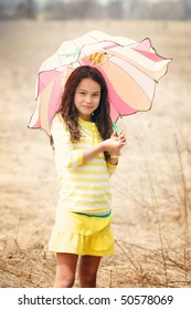 pretty latino girl on a spring day with an umbrella in a field