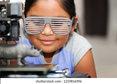 Pretty latino girl wearing 3d printed glasses, looking at her 3d printer as it prints a toy.