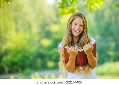 Pretty laughing young girl reads red book, against green of summer park.
