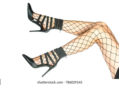 Pretty legs in sexy fishnet stockings and stiletto high heels isolated on white background.