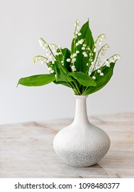 Pretty Lily of the Valley as a floral arrangement in a  white vase on a quartzite counter with copy space