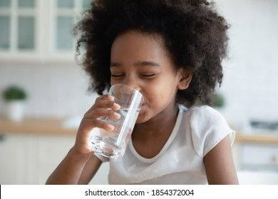 Pretty little African American girl drinking fresh water in kitchen close up, cute preschool child kid holding glass of pure mineral water, enjoying, healthy lifestyle and refreshment concept - Shutterstock ID 1854372004
