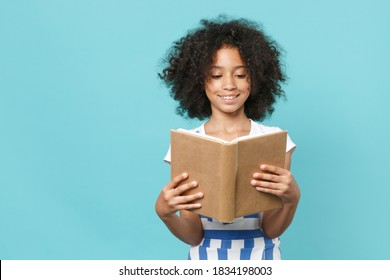 Pretty little african american kid girl 12-13 years old in striped clothes isolated on pastel blue wall background studio portrait. Childhood lifestyle concept. Mock up copy space. Reading book