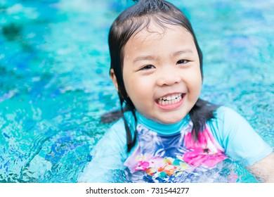 Pretty little asian girl happy in swimming pool.