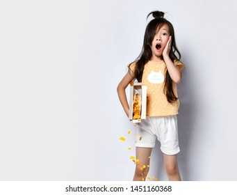 Pretty little asian girl kid in home clothes at the morning during breakfast stands with spilled out corn flakes and moans yawns on gray backgroundwith free text copy space