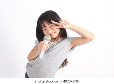 Pretty little asian girl with the microphone in her hand, posting fighting like the voice.