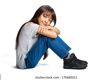 Pretty little asian girl sitting on the floor, Isolated over white