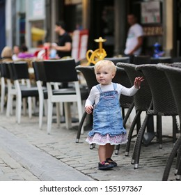 Pretty little baby girl standing next to chair of street cafe summer terrace in a center of big city, at background people are relaxing in cafes and restaurants