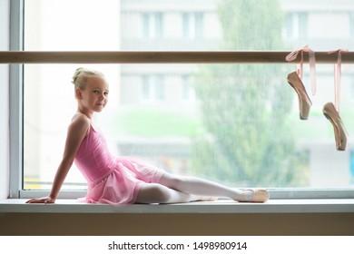 Pretty little ballerina in pink costume. Beautiful teen ballet girl posing on window-sill. Pink ballet shoes hanging on ballet barre.