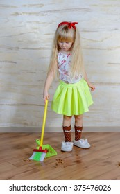 Pretty little blond girl cleaning the house with a colorful plastic toy broom and pan bending forward as she carefully sweeps up the dirt, full length close up