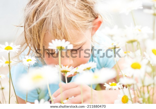 Pretty Little Blond Girl Smelling Daisies on the Beach