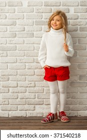 Pretty little blonde girl looking in camera and smiling while standing against white brick wall