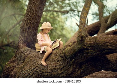 A pretty little blonde girl in a straw hat reading a book on a large spreading tree. Children and science.