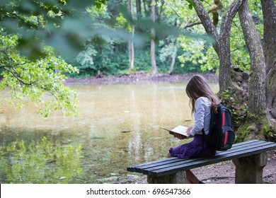 Pretty little blonde schoolgirl with backpack sitting on the bench in the park near lake and reading a book getting ready to go back to school in the nature studying for exam