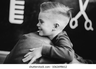 Pretty little boy in a black salon cape in the barbershop.  kid the hairstyle. Wide aperture closeup photo.