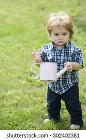 Pretty little boy with blond curly hair in blue checkered shirt and jeans holding white wstering-can looking foward standing on green grass sunny day outdoor copyspace, vertical picture