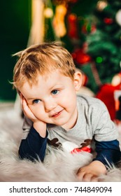 Pretty little boy lies on fluffy carpet before a Christmas tree