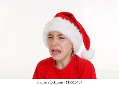 pretty little boy in santa hat crying