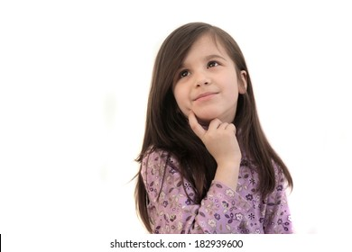 Pretty little brunette 6 year old girl thinking, looking up with finger to face on a white background and copyspace