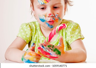 Pretty little child girl painted in the face with candy (childhood, happynes, sweets, holiday concept)
