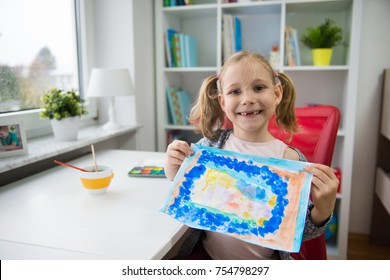 Pretty little child girl painting snowman with colorful paint at home