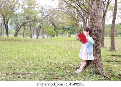 Pretty little child girl reading book in park outdoor standing lean against tree trunk in summer garden.