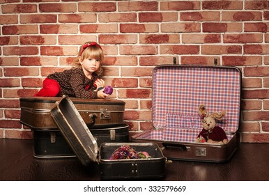Pretty Little cute girl sitting in a big old vintage suitcase on the brick wall background, childhood, games, toys