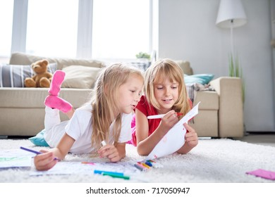Pretty little friends gathered together at cozy living room and enjoying each others company, they lying on carpet and drawing pictures with felt-tip pens