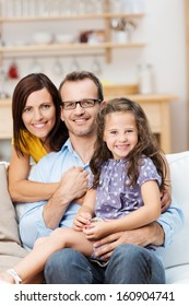 Pretty little girl with a beaming smile sitting on a sofa with her proud parents in a close embrace as they pose for a family portrait