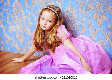 Pretty little girl in beautiful luxurious dress over vintage background. Kid's fashion.