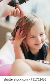 Pretty little girl in black dress sits on the chair and smiles while woman makes curls on her hair