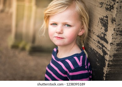 A pretty little girl with blonde hair and bright green eyes leaning against an old concrete pillar posing for a picture