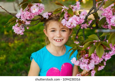 Pretty little girl in blossom cherry garden on beautiful spring day