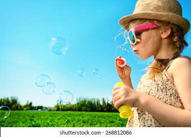 Pretty little girl blows bubbles on a meadow in summer day. Happy childhood. Blue sky.