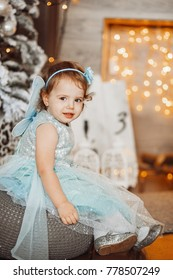 Pretty little girl in blue dress looks funny posing in cosy room decorated for winter holidays