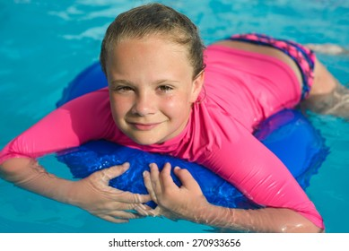Pretty little girl  with blue life ring has fun in the swimming pool