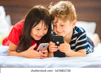 Pretty little girl and boy are playing game console on smartphone and laughing while lie on sofa at home.