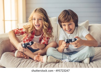 Pretty little girl and boy are playing game console and laughing while sitting on sofa at home