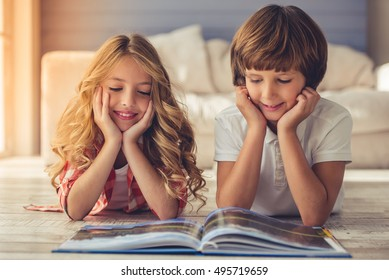 Pretty little girl and boy are reading book and smiling while lying on the floor at home
