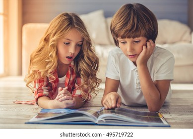Pretty little girl and boy are reading book and showing surprise while lying on the floor at home