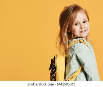 Pretty little girl child in stylish dress and jeans with a yellow backpack behind her back jumping smiling looking at the camera. on yellow studio background