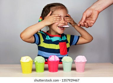 Pretty little girl with closed eyes eating an ice-cream from some different colorful buckets over white background, food and drink concept, portrait studio shot