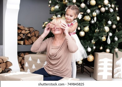 Pretty little girl closing eyes to her grandmother to give a Christmas gift before New Year Tree, merry Christmas concept, happy family, lifestyle indoor, studio shot